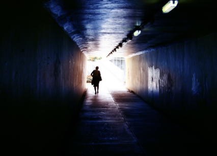 light at the end of a tunnel with woman walking
